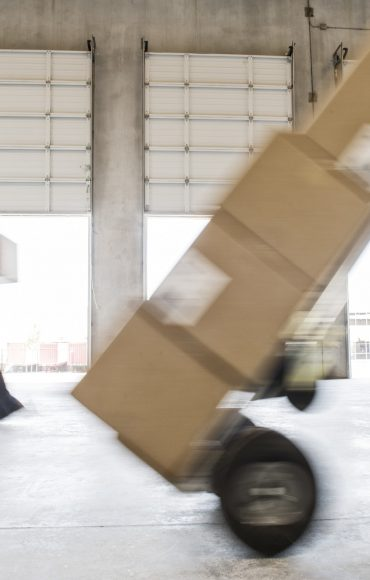 Boxes being moved into a new empty warehouse.